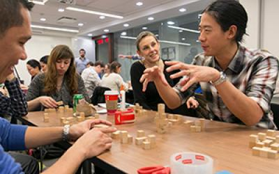 Group of teachers construction a math puzzle with wooden blocks